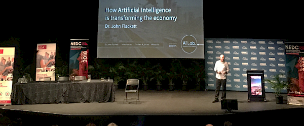 John on stage speaking about AI